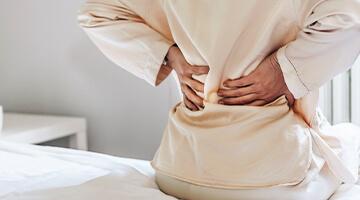 kvinde sidder på seng med ondt i ryggen