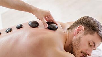 mand får Hot stone massage på ryg